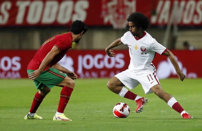 Akram Afif dari Qatar beraksi dengan Goncalo Guedes dari Portugal
